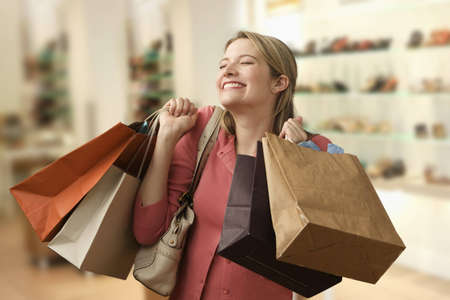 Beautiful young woman shows an ecstatic expression while holding shopping bags in a store.  Horizontal shot. photo