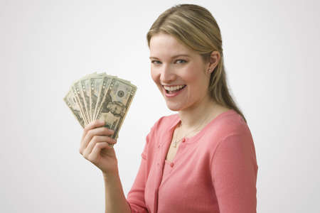 A young woman is holding up cash in a fan and smiling at the camera.  Horizontal shot. Stock Photo