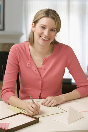 Beautiful young woman smiles at the camera while writing a letter.  Vertical shot.