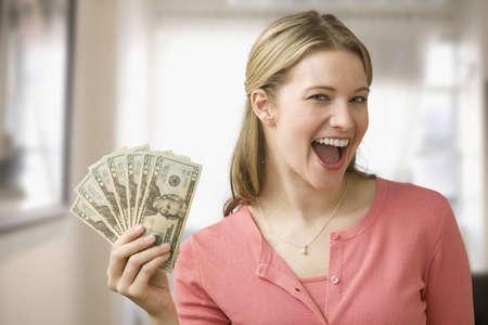 Eine junge Frau ist holding up Bargeld in ein Fan und L�cheln in die Kamera. Horizontale erschossen.