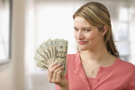 Eine junge Frau ist holding up Cash in ein Fan und L�cheln in die Kamera.  Horizontal gedreht.