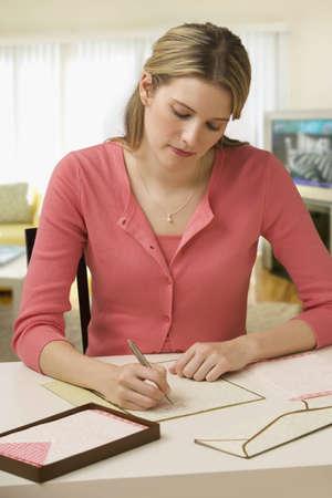 persona escribiendo: Concentrados de la joven y bella mujer mientras escrib�a una carta en su escritorio. Un disparo vertical.