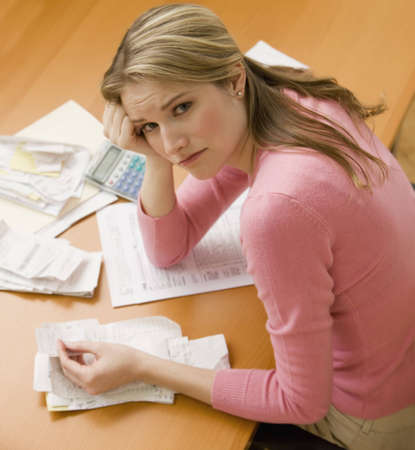 burden: A young woman looks upset while sorting through her old receipts.  Square shot.