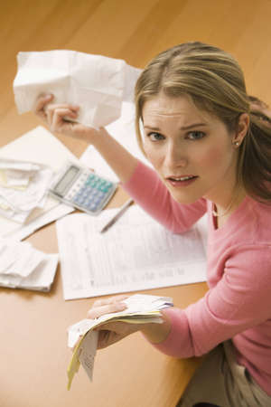 impuestos: Una joven busca malestar mientras ordenar a trav�s de sus antiguos recibos. Un disparo vertical.