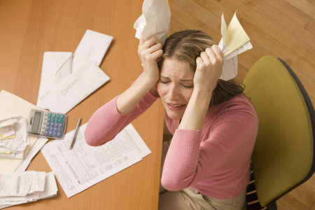 Eine junge Frau ist Rechnungen bezahlen, an Ihrem Schreibtisch und hat ihre Augen geschlossen von Stress. Horizontale erschossen.