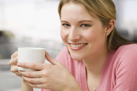 A young woman is holding a coffee cup while smiling at the camera.  Horizontal shot. Stock Photo
