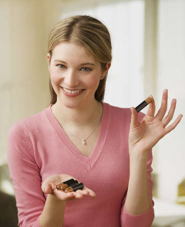 Attractive young woman holds up a set of AA batteries in her hands.  Vertical shot.