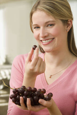 concord grape: An attractive young woman is eating grapes while smiling at the camera.  Vertical shot.