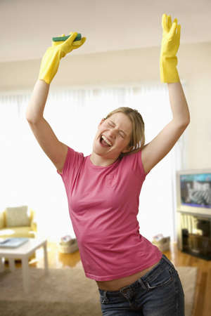 housecleaning: Young woman with housecleaning gear dances in the living room.  Vertical shot.
