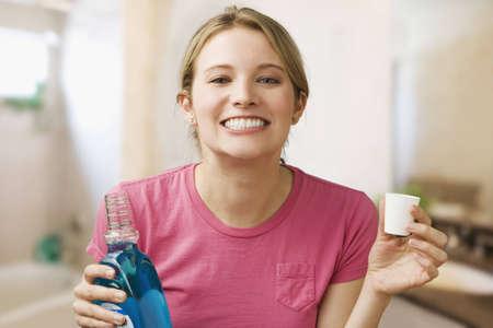 enjuague bucal: Una joven mujer muestra sus dientes mientras mantiene una botella de enjuague bucal. Horizontal a tiros.