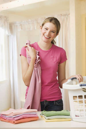 A young woman is folding laundry and smiling at the camera.  Vertical shot. Stock Photo