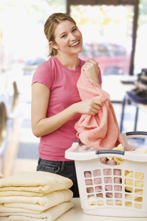 folding camera: A young woman is folding laundry and smiling at the camera.  Vertical shot. Stock Photo