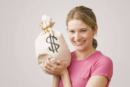 An attractive young woman holds up a bag of money while smiling at the camera.  Horizontal shot.
