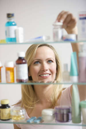 A young woman reaches for a container in her medicine cabinet.  Vertical shot. Stock Photo - 7466823