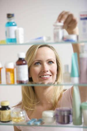 의학: A young woman reaches for a container in her medicine cabinet.  Vertical shot.