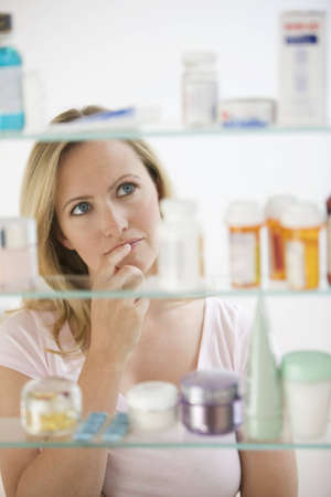 medicine cabinet: A young woman is looking through her medicine cabinet.  Vertical shot.