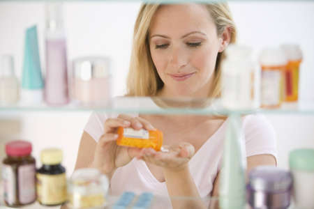 A young woman pours out medicine into her hand.  She is visible through her medicine cabinet.  Horizontal shot. Stock Photo