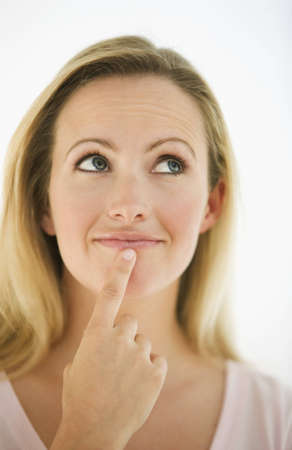 Eine junge Frau hat den Finger auf Ihrem Kinn, wie Sie denkt.  Sie sucht nach oben und Weg von der Kamera.  Vertikal gedreht.