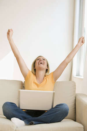 A young woman sitting on the couch with a laptop throws her arms in the air while cheering.  Vertical shot. Stock Photo - 7466647