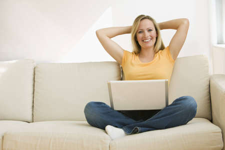 A young woman sits back on the couch with a notebook computer in her lap and her hands behind her head.  Horizontal shot. photo