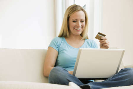 A young woman is working on a laptop and holding up her credit card.  Horizontal shot. photo