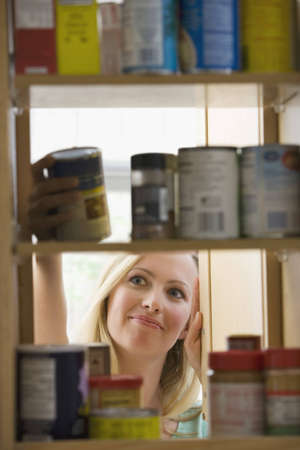 ingredient: A young woman is smiling as she looks through kitchen cupboards.  Vertical shot.