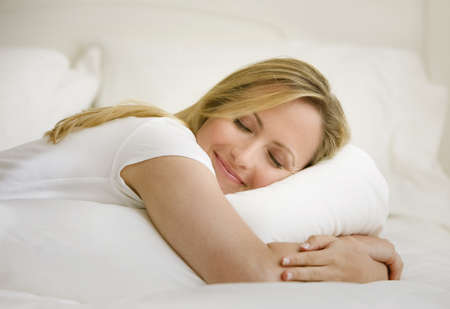 A young woman is lying on her bed with her eyes closed.  She is embracing a pillow.  Horizontal shot. Stock Photo