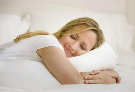 woman bed: Una mujer joven est� acostado en su cama con sus ojos cerrados. Ella es abrazar una almohada. Horizontal a tiros.  Foto de archivo