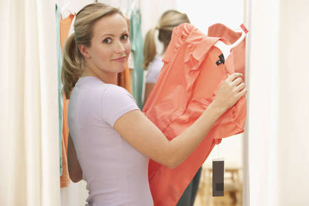 A young woman poses with clothing she has picked out in a store.  Horizontal shot. Stock Photo - 7466871