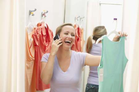 A young woman is holding up a dress in a store while talking on a cell phone.  Horizontal shot.