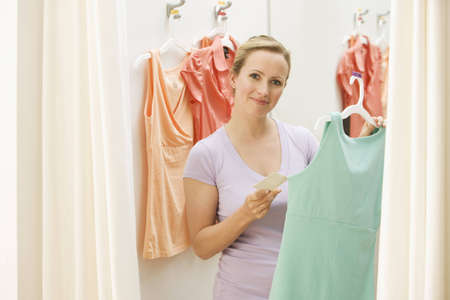 A young woman poses with clothing she has picked out in a store.  Horizontal shot. Stock Photo