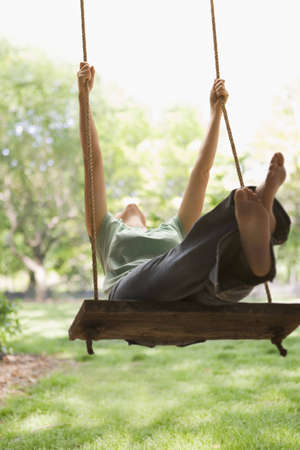 A young woman is swinging on a swing in a park setting.  Vertical shot. Stock Photo