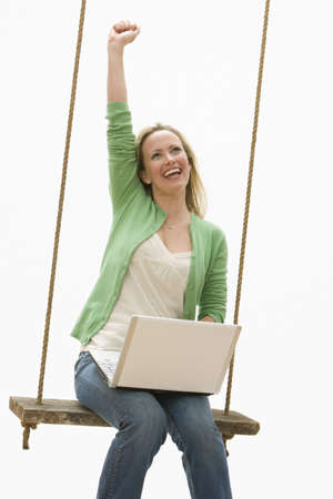 A young woman is sitting on a swing while working on a laptop.  She is raising a fist into the air.  Vertical shot. Stock Photo