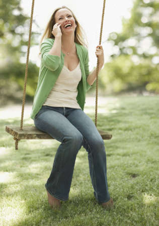 A young woman is sitting on a swing as she talks on her cellphone.  Vertical shot.