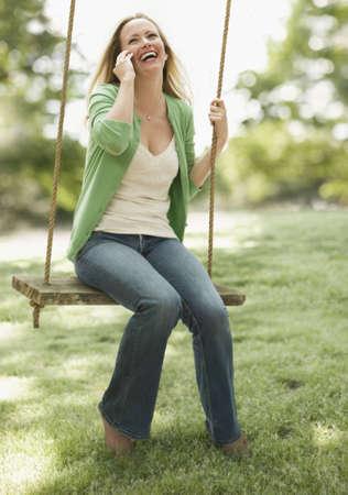 Eine junge Frau sitzt auf einer Schaukel, wie Sie auf Ihr Handy spricht. Vertikal gedreht.