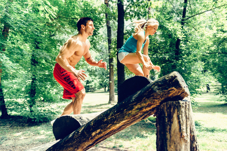 recreational climbing: Attractive young couple crossing obstacles on a fitness trial