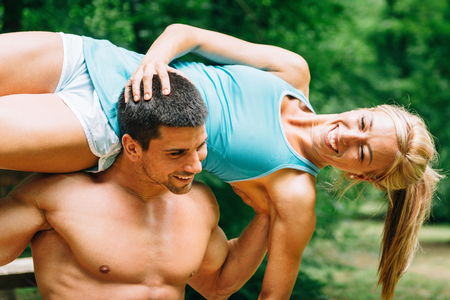 man carrying woman: Young couple exercising in nature. Man carrying woman on his shoulders Stock Photo