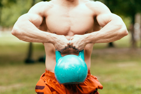 kettle bell: Muscular man exercising with kettle bell