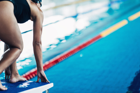 freestyle: Freestyle swimmer on starting block, ready to jump Stock Photo