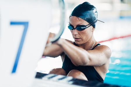 backstroke: Female backstroke swimmer on starting block Stock Photo