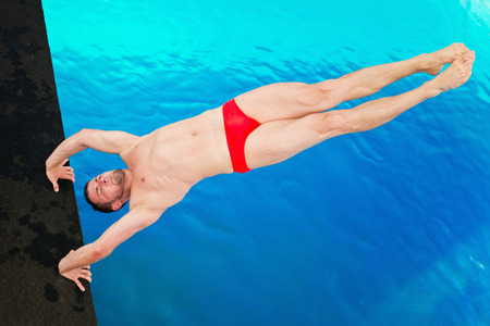 handstand: Platform diving competitor, taking off from handstand, shot from above Stock Photo