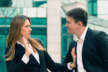 sex discrimination: Workplace harassment - young business woman stopping aggressive colleague Stock Photo