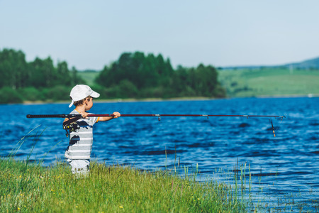 only 3 people: Funny little boy trying to fish