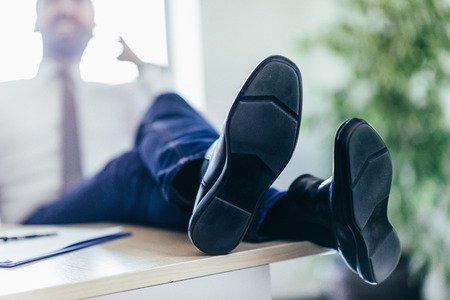 hands lifted up: Businessman relaxing in office, talking over the phone with feet on desk. Selective focus on shoes. Toned image Stock Photo