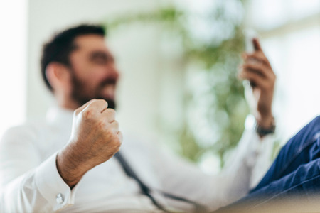 fist: Businessman getting good news over smart phone, fist pumping. Selective focus on fist Stock Photo