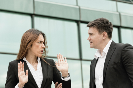 sex discrimination: Aggression at work - manager with aggressive attitude towards younger female coleague Stock Photo