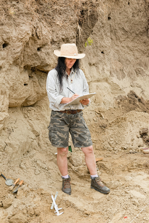 archaeologist: Archaeologist at excavation site, taking notes