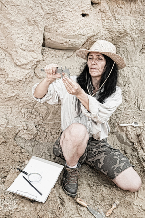 Archeology - researcher determining measurements of an ancient coin found at arceheolgy site