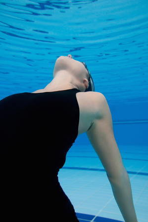 alienated: Estranged faceless woman floating in a cold environment. Underwater, wide angle, close-up Stock Photo