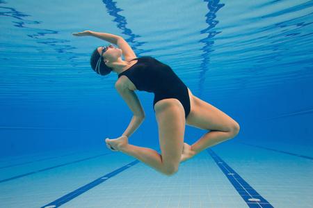 natación sincronizada: bailarina de danza moderna realizar bajo el agua en una piscina grande. Poste procesado, añadió grano